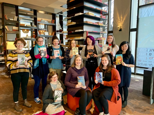 Members of the 2019 Amelia Bloomer Project committee pose with their Top Ten books in front of some bookshelves